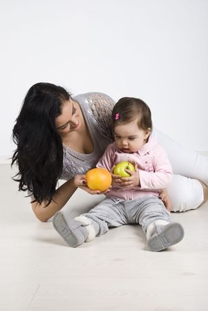 Young mother sitting on wooden floor with her baby girl and giving her child fruits  photo
