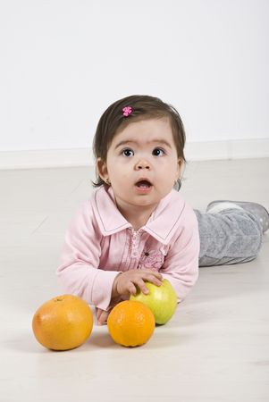 Attentive baby girl lying down on laminate flooring playing with fruits and looking up photo