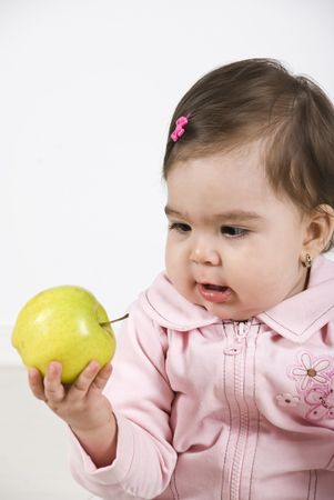 Amazed baby girl 11 months old holding a green apple in her hand and looking amazed to fruit Stock Photo - 6836969