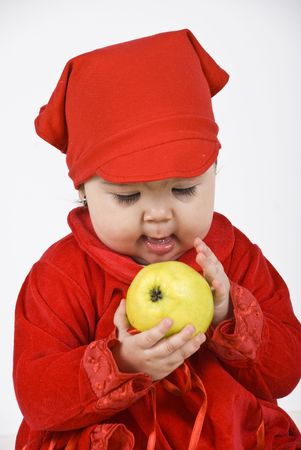 caress: Smiling baby girl 11 months old holding and caress a green apple Stock Photo