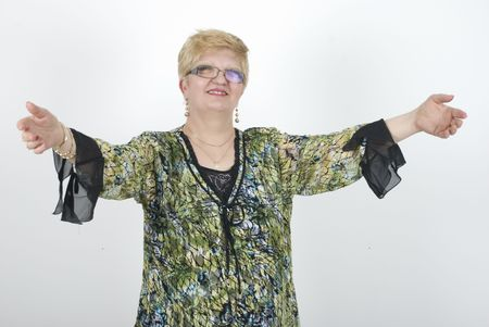 Mature woman standing with open hands to welcoming or to hug someone photo