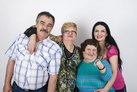 Happy family with  three generations of women grandmother,mother ,daughter and father  posing in a big embrace ,elderly woman pointing to you photo