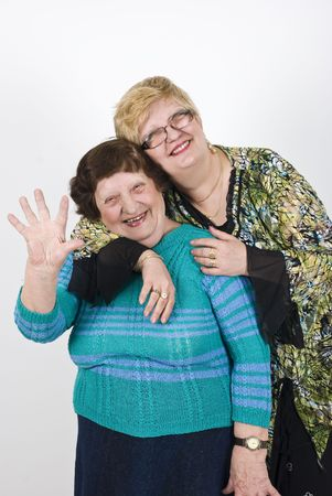 Happy mature woman daughter embracing her elderly  mother and  older woman laughing and  waving Stock Photo - 6871286