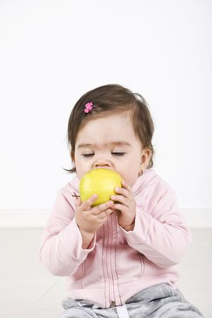 Baby girl bite an apple and enjoying with eyes closed ,copy space for text message photo