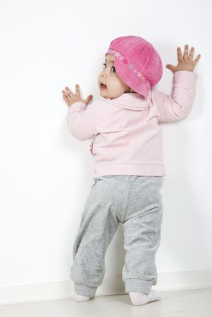 Back of full body baby girl 11 months old standing with hands on wall and looking away over her  shoulder photo