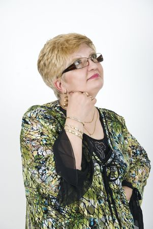 Mature woman with glasses thinking ,holding hand on chin and looking up photo