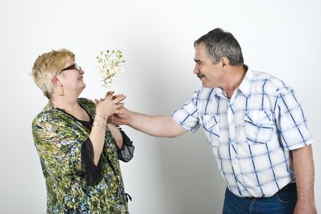 Middle aged man giving flowers to his wife and the woman looking surprised photo