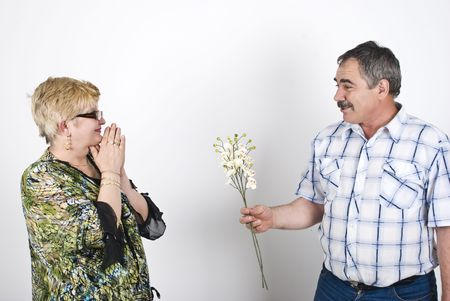 Middle adult husband offering flowers to her wife and she is excited and pleasantly surprised photo