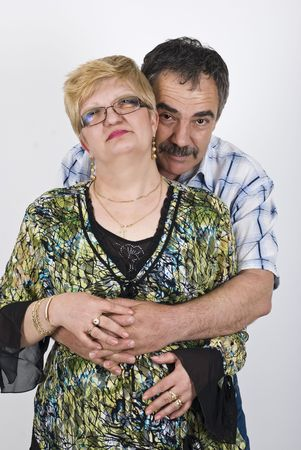 Middle adult couple standing in a hug and smiling photo