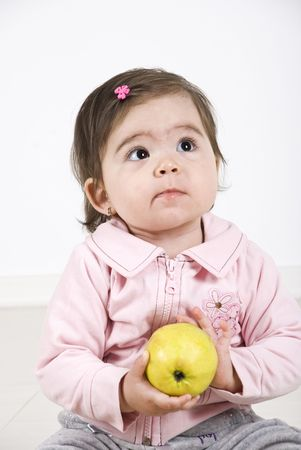 Thinking baby girl holding an apple in her hands and looking away photo
