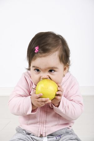 Baby girl sitting on floor and trying to bite an apple photo