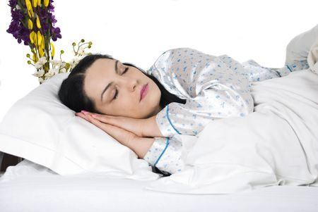 Beautiful woman sleeping with hand behind face in bed photo