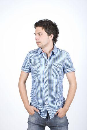 jeans apretados: J�venes de moda a hombre posando ap�sito en estrecha de pantalones vaqueros y camisa moderno con plazas, mirando de lejos