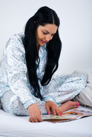 Woman sitting with legs crossed in bed and reading a magazine photo
