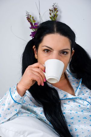 nightclothes: Portrait of beautiful woman drinking a cup of coffee in the morning