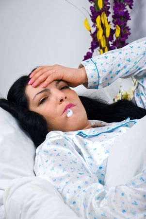 Sick woman having flu and fever lying in bed taking temperature with thermometer and holding hand on head photo