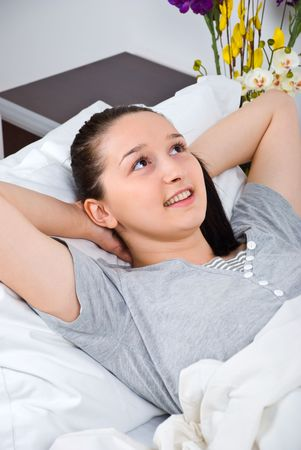 Thinking young woman lying in bed and relaxing photo
