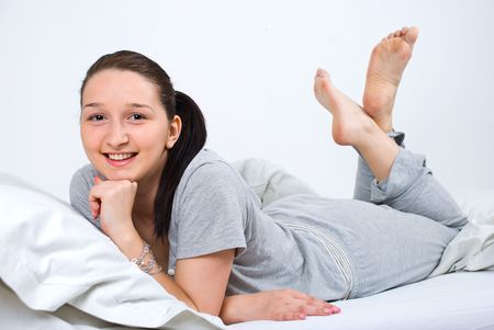 Happy young woman lying in bed with legs up photo