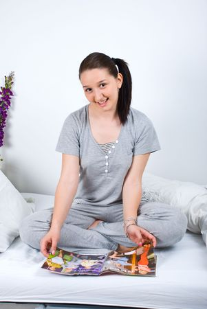 nightclothes: Happy young female in pajamas sitting in bed and reading magazine