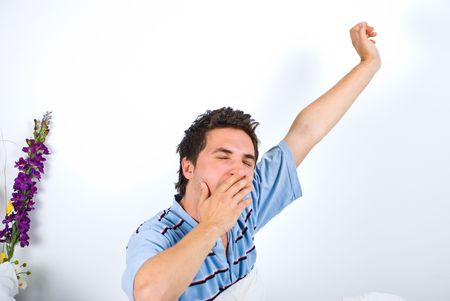 Young man stretching his hand while yawning and holding the other hand to mouth Stock Photo - 6960463