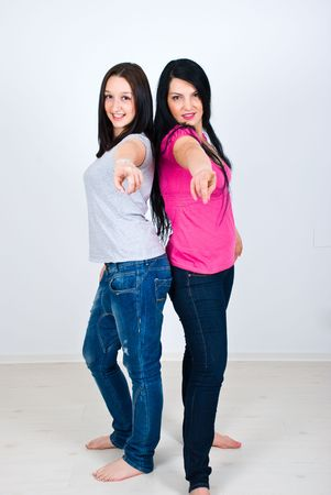 Two happy women in casual clothes standing back to back and pointing to you photo