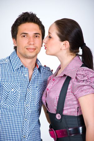 Fashion models couple  wearing  squares shirts  standing  in embrace and woman preparing to kissing him photo