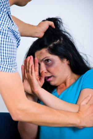 paliza: Aterrorizados maltratada mujer tratando de detener el ataque y defenderse,
