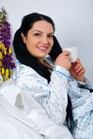 nightclothes: Beautiful morning woman lying in bed  and holding a cup of coffee Stock Photo