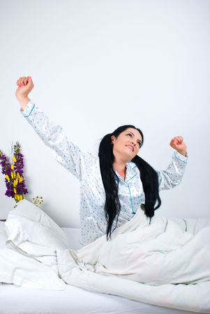 Happy woman waking and stretching hands in the morning,copy space for text message photo