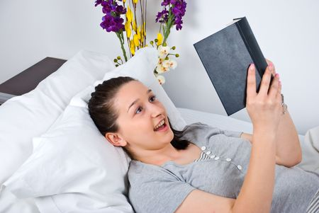 nightclothes: Woman lying on bed reading a captivate  book and looking surprised Stock Photo