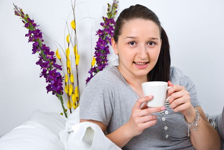 nightclothes: Woman enjoying a cup of coffee in the morning in her bed