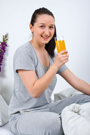 nightclothes: Happy woman relaxing on bed and holding a fresh orange juice in the morning