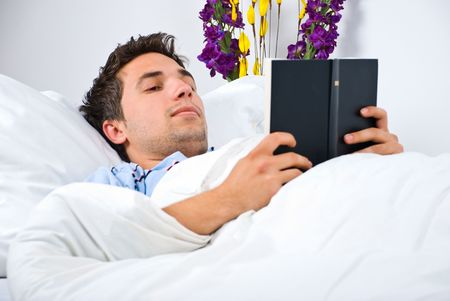 nightclothes: Young man read a book on bed before sleep Stock Photo