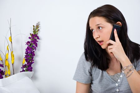 Young woman sitting in bed and talking at cell phone ,looking away,copy space for text message photo