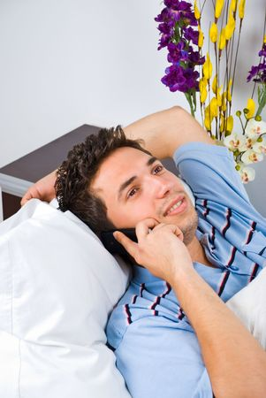 Young man lying down on bed talking by phone mobile and smiling photo