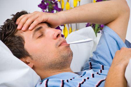 fieber: Nahaufnahme von jungen Mann liegend im Bett nehmen Temperatur und mit Grippe