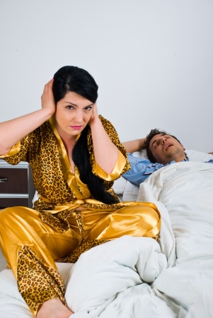 snoring: Couple in bed with woman awake and nervous because cant sleep and holding hands on ears while man sleeping and snoring