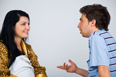 nightclothes: Close up of young couple on bed having an conversation and the man explaining something to his wife Stock Photo