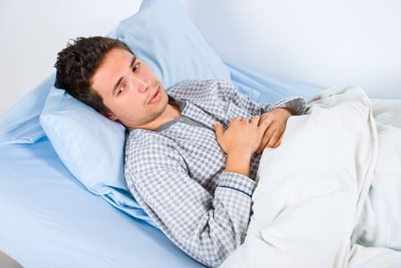 Patient man lying on bed in hospital having pain and looking away photo