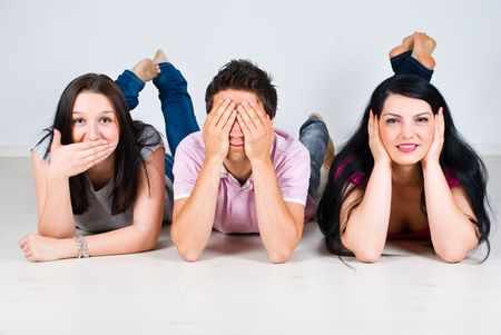 Three cheerful friends lying down on wooden floor and gesturing speak,see and hear no evil Stock Photo - 6960514