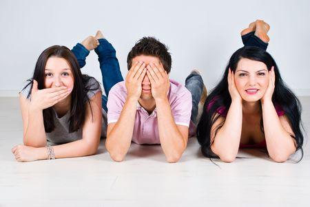 escuchar: Tres amigos alegres acostado en el piso de madera y ensaya un juego brillantes hablan, ver y no o�r ning�n mal Foto de archivo