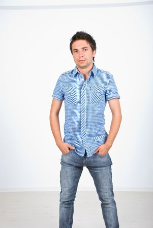 Fashionable young man in jeans and squares shirt posing Stock Photo - 6960518