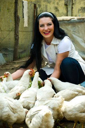 Laughing woman feeding  big farm chickens and having fun photo