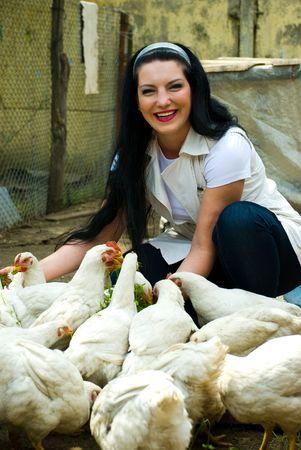 aves de corral: Riendo a mujer alimentaci�n de pollos de granja grandes y divirti�ndose Foto de archivo