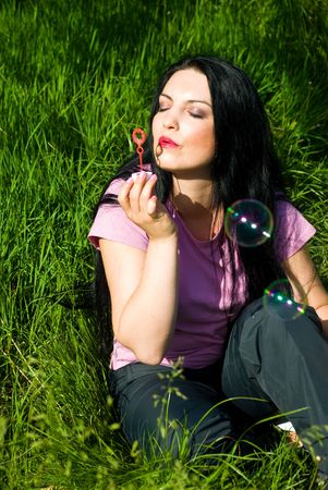 Beautiful woman relaxing in green grass and enjoying a sunny day making soap bubbles photo