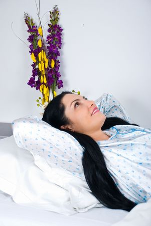Smiling woman relax in bed  with hands under head looking up photo