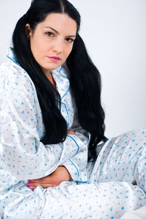 Young woman  in pajams sitting on bed and having a severe stomach ache holding hands on abdomen photo