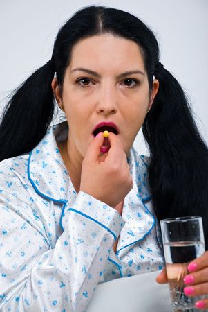 Sick woman taking a pill and holding a glass with water Stock Photo - 6960539