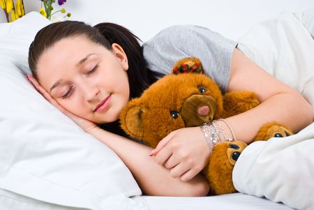 Beauty woman sleeping in her bed and holding a stuffed bear photo