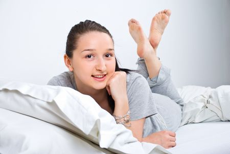 Happy young female lying on bed barefoot and smiling photo